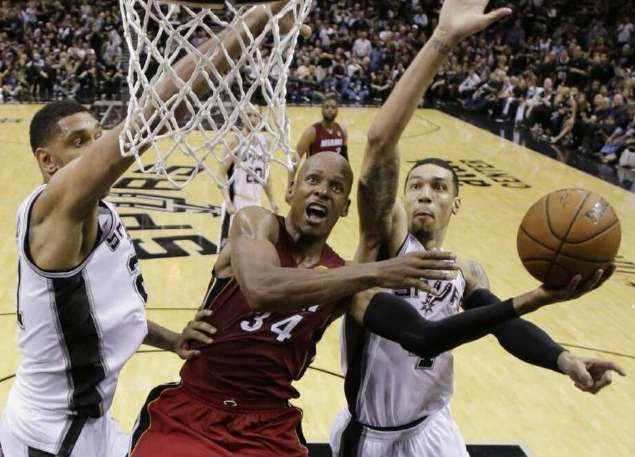 The Miami Heat's Ray Allen, center, is doubled at the basket by the Spurs' Tim Duncan, left, and Danny Green. The Spurs won Game 1 of the NBA Finals, taking a 110-95 victory. Photo: Eric Gay