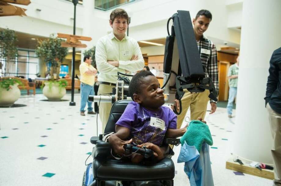 Dee Faught picks up a shirt with a robot arm installed on his motorized wheelchair by Rice University students including Sergio Gonzalez, standing at left, and Nimish Mittal, right. Photo: Jeff Fitlow