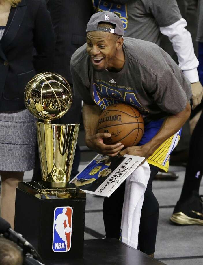 Golden State Warriors guard Andre Iguodala looks at the championship trophy after the Warriors won the NBA Finals Wednesday night in Cleveland Photo: Darron Cummings