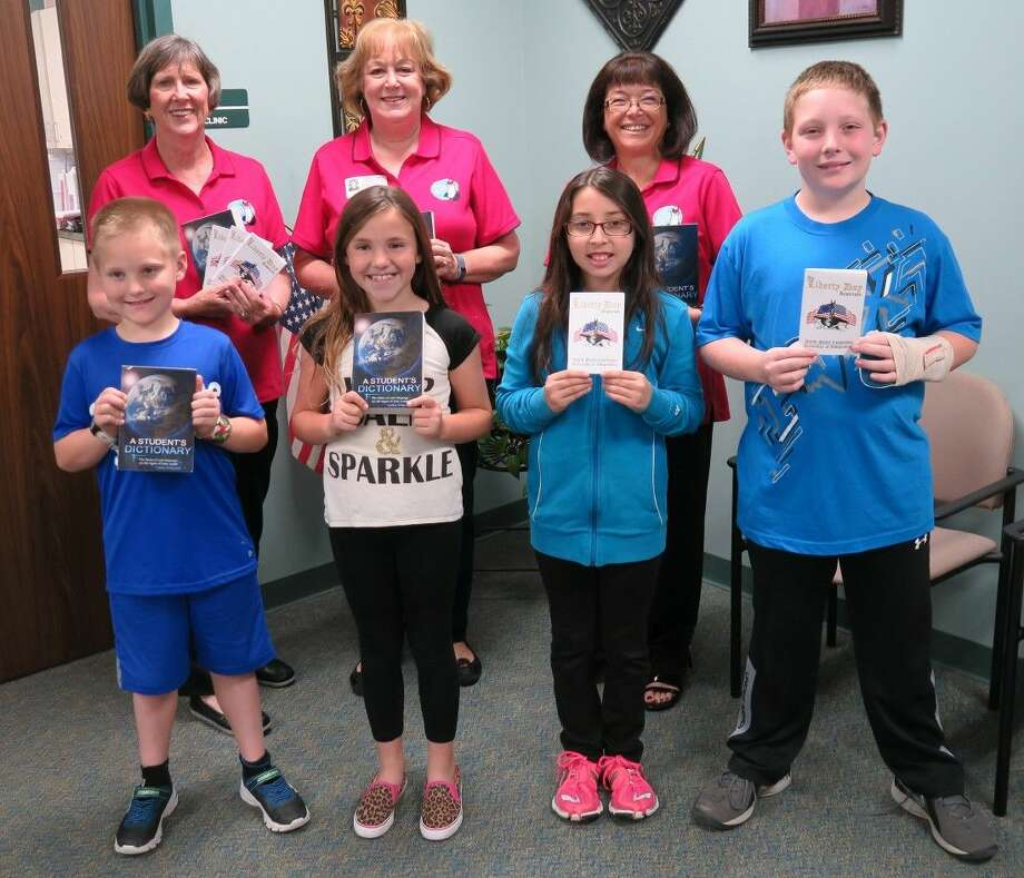 Front row: Dictionaries were presented to Meador Elementary third grade students Colson Solberg and Mallori Mitchell, and Belkys Benitez and Carson Haefner, fifth graders, received Constitution booklets.Back row, Ann Kate, NSRW Media Chairman; Judy Love, NSRW Literacy/Youth Outreach Chairman; and Gail McKinnon, NSRW President.