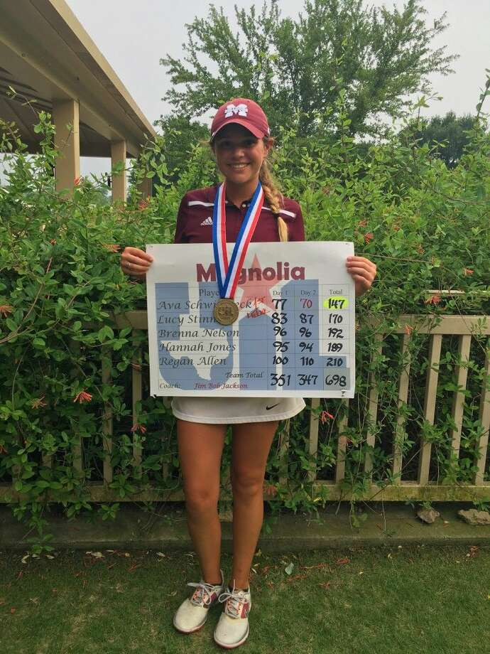 Ava Schwienteck holds up her team's score chart after winning the 2016 UIL Class 5A State Golf Championship.