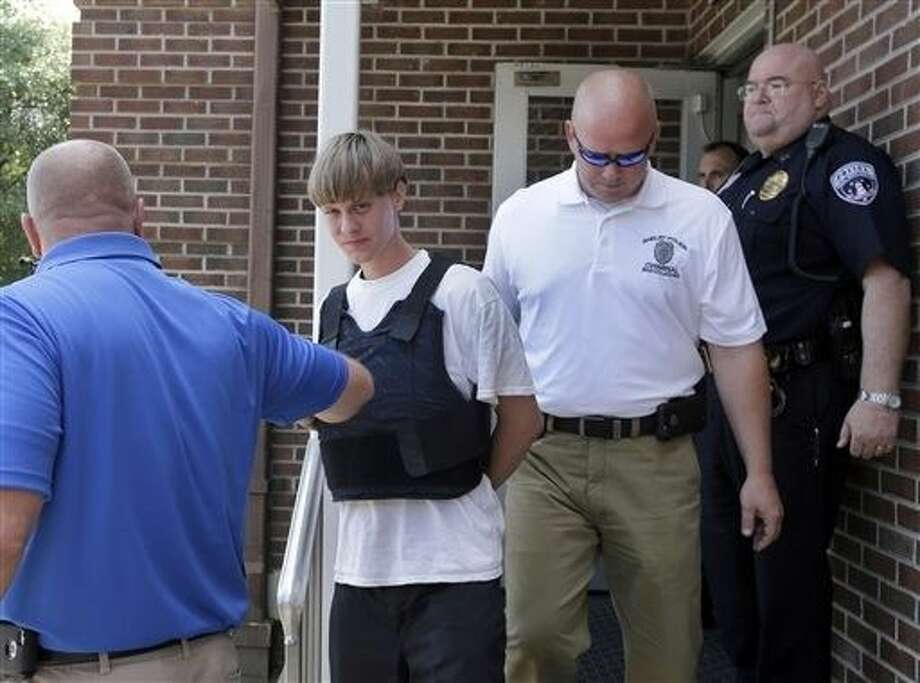 Charleston, S.C., shooting suspect Dylann Storm Roof, center, is escorted from the Shelby Police Department in Shelby, N.C., Thursday Photo: Chuck Burton