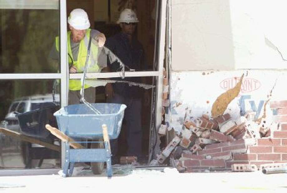 Workers help clean up broken glass and bricks at Panera Break after a 64-year-old woman lost control of her car, hitting the exterior of the building and injured an employee on College Park Dr. Tuesday. / Conroe Courier / HCN
