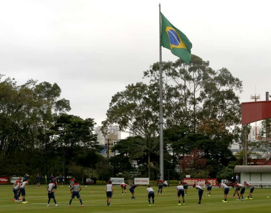 United States players stretch at the beginning of a training session as a Brazilian flags flies in the background on Monday at the Sao Paulo Futebol Club in Sao Paulo.