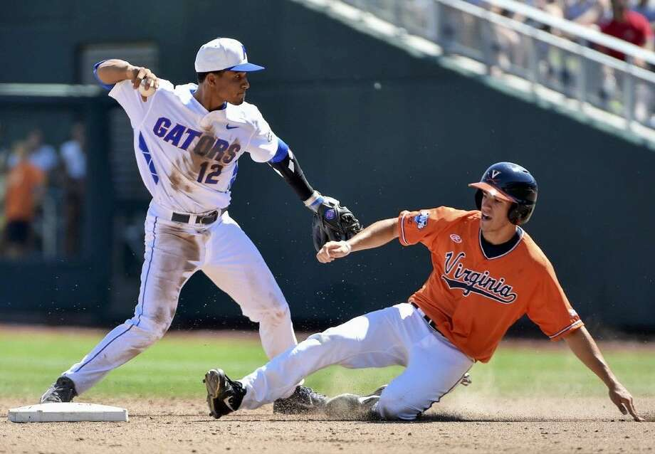 Florida shortstop Richie Martin (12) throws to first base for a double play after forcing out Virgina's Adam Haseley, in the fifth inning of an NCAA College World Series at TD Ameritrade Park in Omaha, Neb., Friday. Photo: Mike Theiler