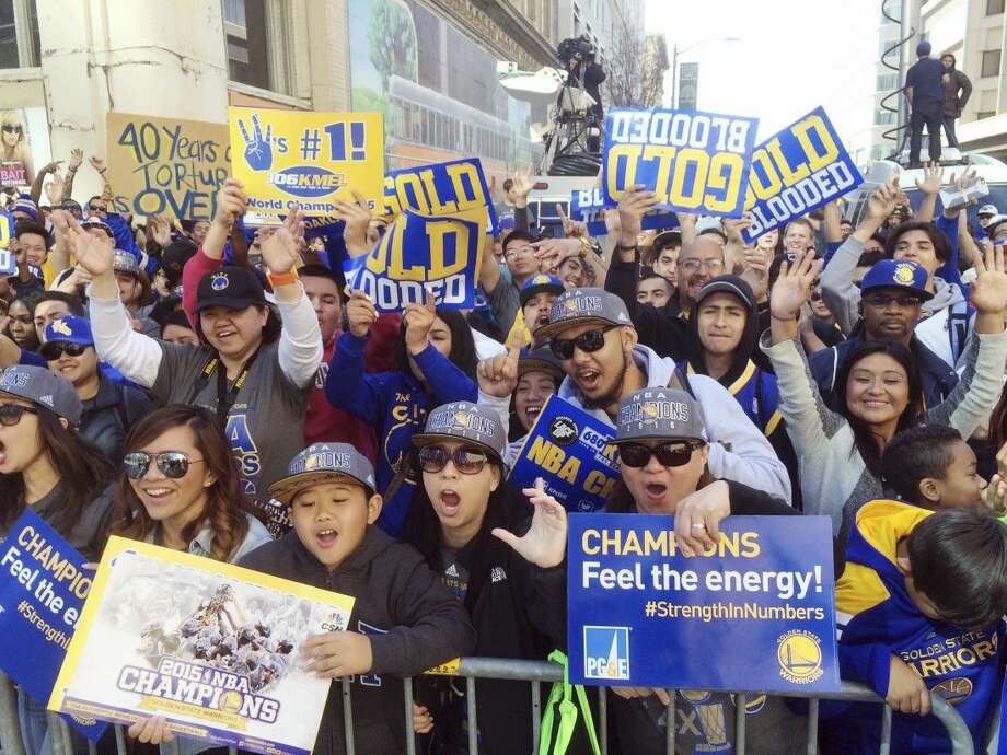 Golden State Warriors fans cheer from behind barricades for a parade in Oakland, Calif. Friday. Photo: Jeff Chiu