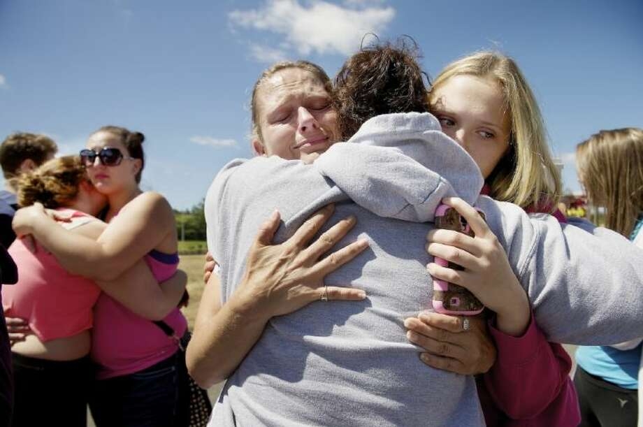 Brandi Wilson, left, and her daughter, Trisha Wilson, 15, right, embrace Trish Hall, a mother waiting for her student, as students arrived at the Fred Meyer grocery store parking lot in Wood Village, Ore., after a shooting at Reynolds High School Tuesday in nearby Troutdale.