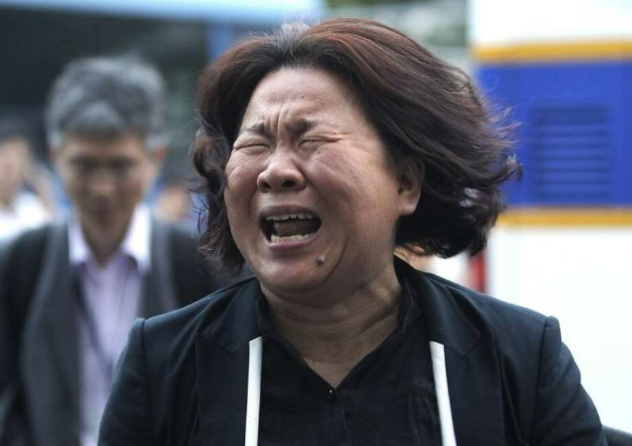 A family member of passengers aboard the sunken ferry Sewol cries after a pretrial hearing of crew members of the ferry at Gwangju District Court in Gwangju, South Korea, Tuesday.