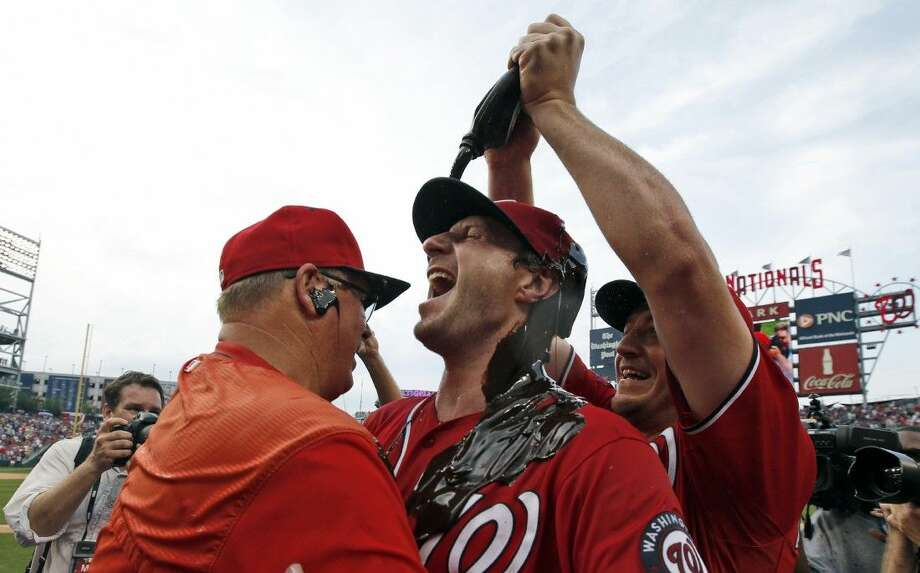 Washington Nationals' Jordan Zimmermann, right, douses starting pitcher Max Scherzer with chocolate syrup as Scherzer hugs pitching coach Steve McCatty, left, after Scherzer's no-hitter baseball game against the Pittsburgh Pirates at Nationals Park, Saturday. Photo: Alex Brandon