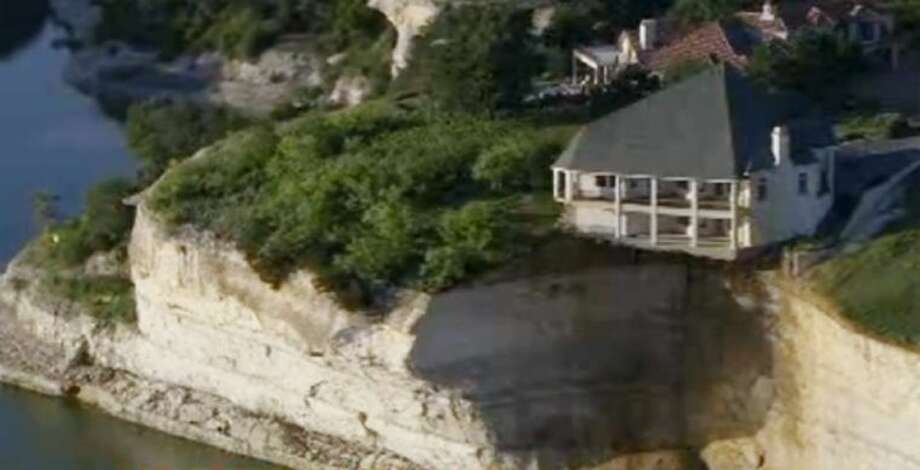 In this image taken from video provided by WFAA-TV on Tuesday, a luxury house teeters on a cliff about 75 feet above Lake Whitney. WFAA-TV reported Wednesday that the house has been condemned and the owners evacuated about two weeks ago.