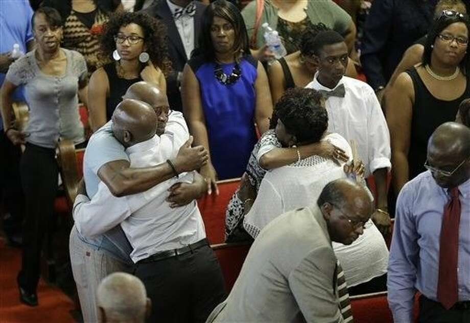 Parishioners embrace at the Emanuel A.M.E. Church Sunday in Charleston, S.C., four days after a mass shooting that claimed the lives of its pastor and eight others. Photo: David Goldman