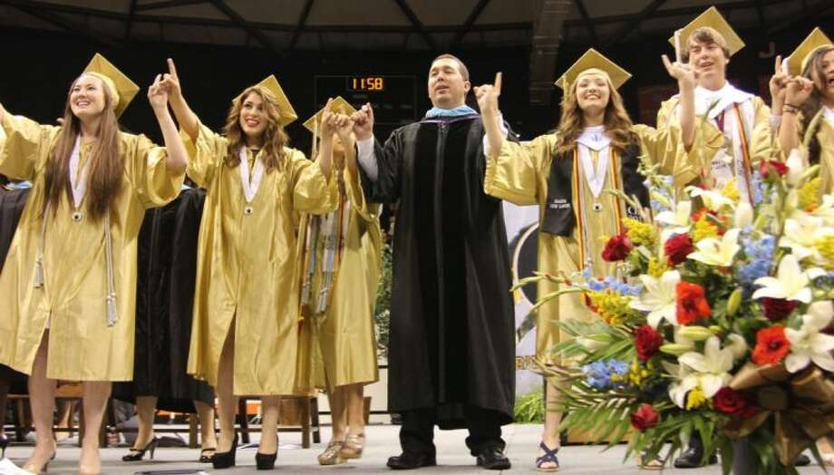 Dr. Mark Weatherly joins in singing with the Class of 2014 choir graduates at Conroe High School's graduation May 31, the last graduation to be held at Johnson Coliseum in Huntsville.