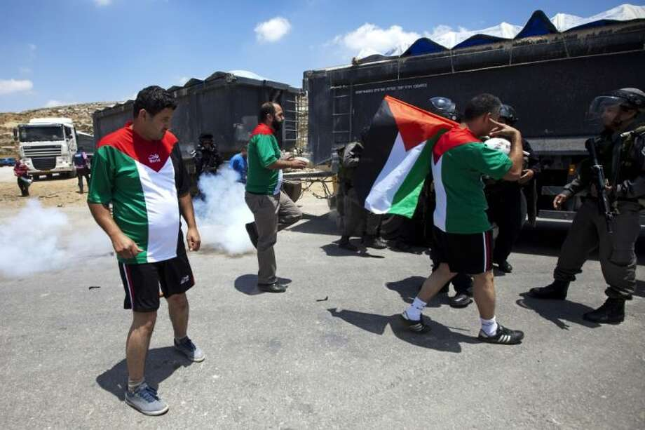 Israeli border policeman and Palestinian protesters argue during a demonstration in support for dozens of Palestinian hunger strikers in Israeli jails, outside Ofer military prison, near the West Bank city of Ramallah Wednesday.