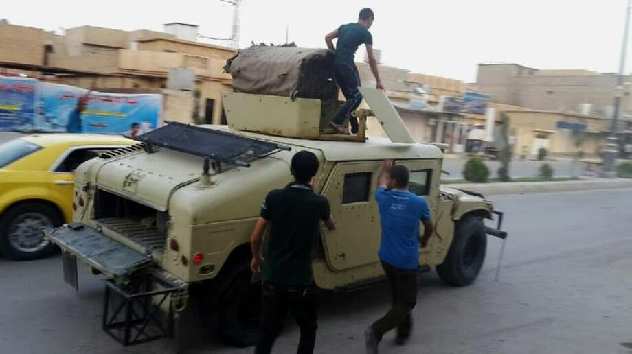 Teenagers ride on an armored vehicle belonging to the Iraqi army in Tikrit, 80 miles north of Baghdad, Iraq, Wednesday..