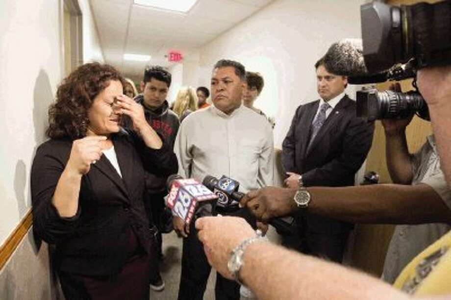 Jacqueline Rios speaks to the media as her husband, Juan Cuyun, center, looks on after former Conroe Police Department Sgt. Jason Blackwelder was sentenced to five years probation for the murder of her son, Russell Rios, in Conroe Wednesday. Rios was shot in the head after fleeing from a Walmart in Conroe after allegedly stealing iPad cases on July 31, 2013. Photo: Jason Fochtman / Conroe Courier / HCN