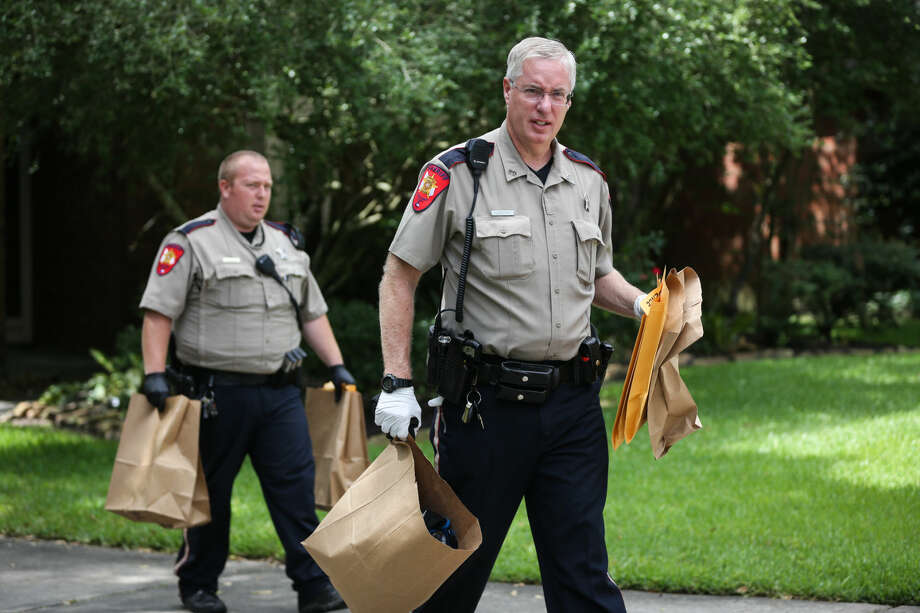 Deputies with the Montgomery County Sheriff's Office carry out bags of evidence after executing a search warrant at a home on Bonneymead Circle in The Woodlands Monday.