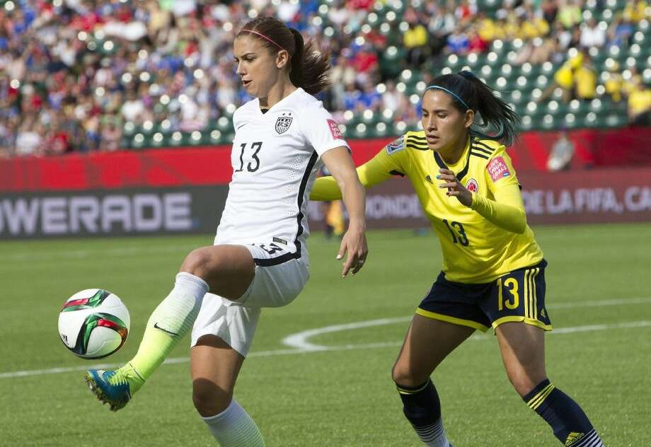 The United States' Alex Morgan (13) keeps the ball away frpm Colombia's Angela Clavijo in Edmonton on Monday night. The Americans advance to the Women's World Cup quarterfinals with a 2-0 victory. Photo: JASON FRANSON