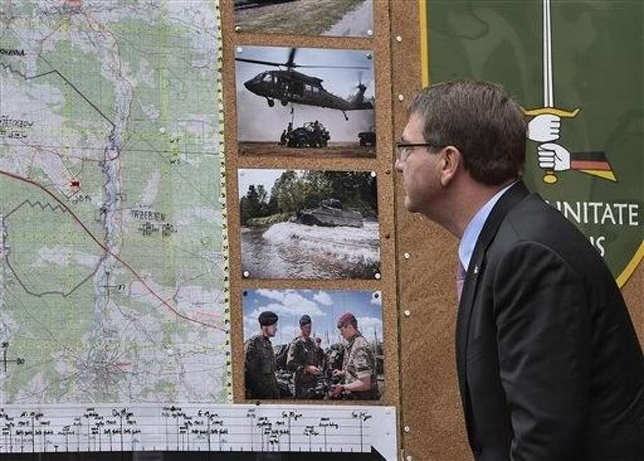 US Secretary of Defense Ash Carter looks at pictures of a maneuvers during his visit to the I. German-Dutch Brigade in Muenster, Germany, Monday. Photo: Martin Meissner