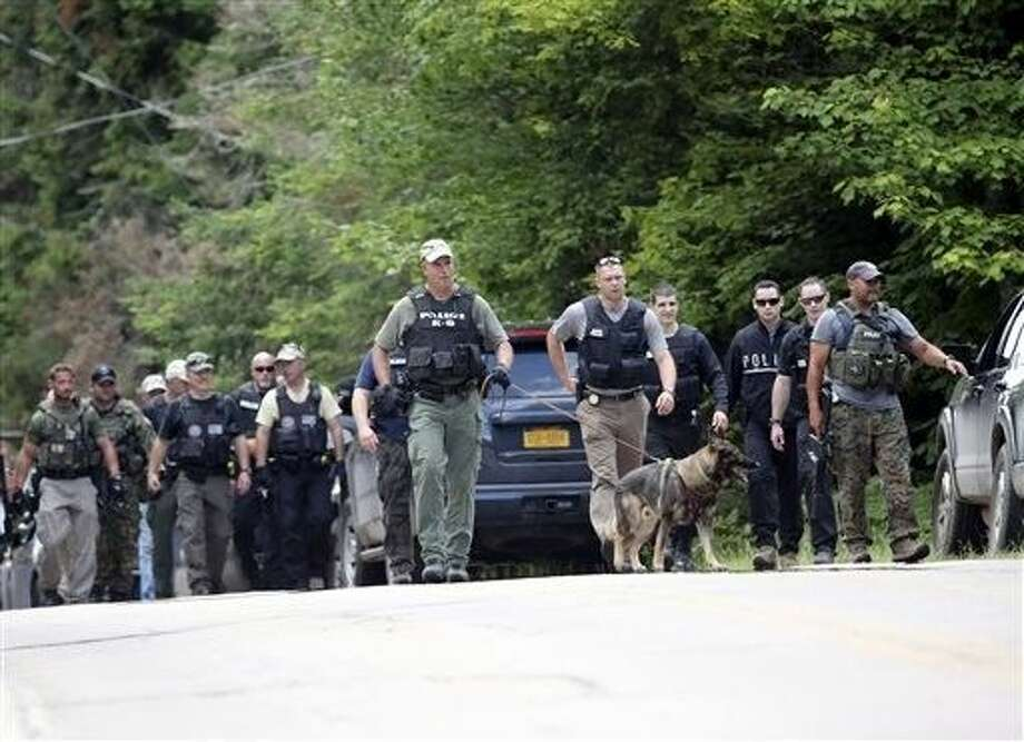 Law enforcement officers walk along a road as the search continues for two escaped prisoners from the Clinton Correctional Facility in Dannemora, on Monday in Owls Head, N.Y. In the more than two weeks since inmates David Sweat and Richard Matt escaped, more than 800 law enforcement officers have gone door-to-door checking houses, wooded areas, campgrounds and summer homes. Photo: Mike Groll