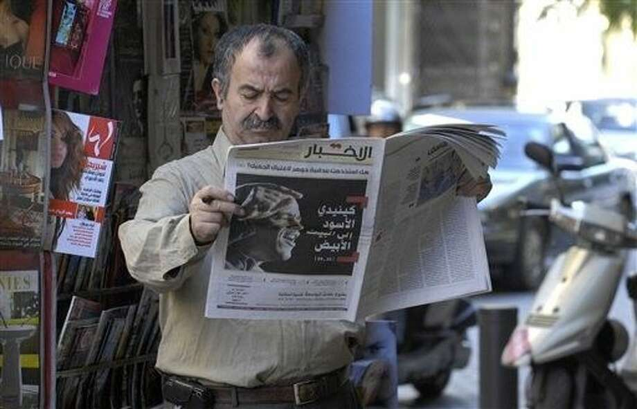 "FILE - In this 2008 file photo, a man reads al-Akhbar newspaper covering Barack Obama's victory in the U.S. Presidential election with a banner headline ""The Black Kennedy to the White House,"" in Beirut. Saudi diplomatic correspondence published by the WikiLeaks group backs long-held suspicions the kingdom is using its oil wealth to buy influence with media and research centers across the Arab world. ""Buying Silence,"" was the Saturday headline in Beirut's pro-Hezbollah Al-Akhbar daily, which is critical of Saudi Arabia, describing the revelations in the cables. Photo: Ahmad Omar"