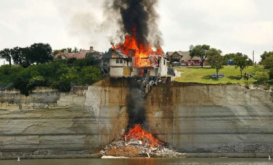 A gated community White Bluff home is burned to save Lake Whitney from falling debris Friday.
