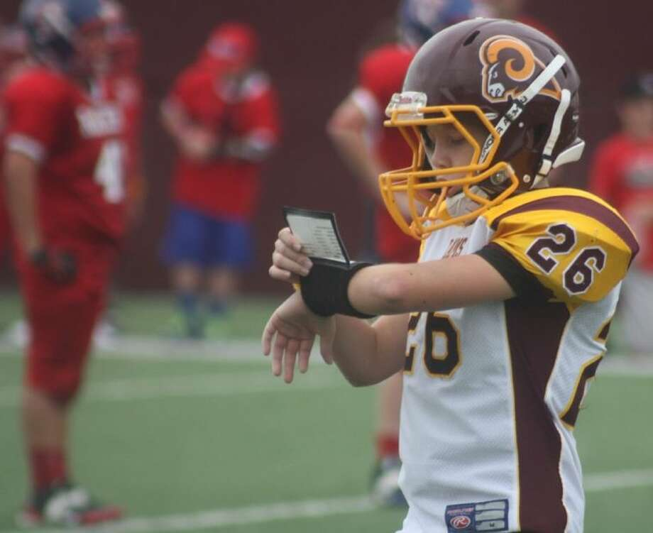 Deer Park Senior Rams quarterback Hunter Williams checks his wristband playcall list as the coaching staff looks for a play that will put a dent in the Clear Lake Space Raiders defense during last Saturday's TIFI contest at Clyde Abshier Stadium. Photo: Robert Avery