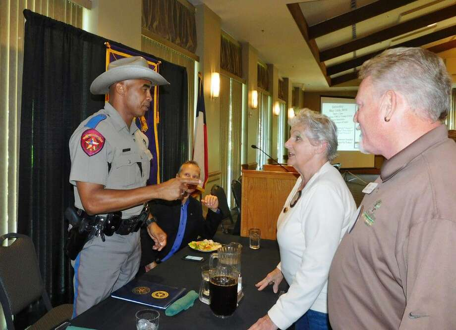 Texas Highway Patrolman Erik Burse, left, visits with Conroe Noon Lions Club members Virginia Clement, center, and Ed Dolphin, right, during his presentation last week at the Lone Star Convention Center.