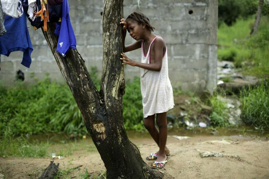 Mercy Kennedy, 9, cries after learning of her mother's death on Oct. 2, 2014, outside her home in Monrovia, Liberia. Photo: Jerome Delay