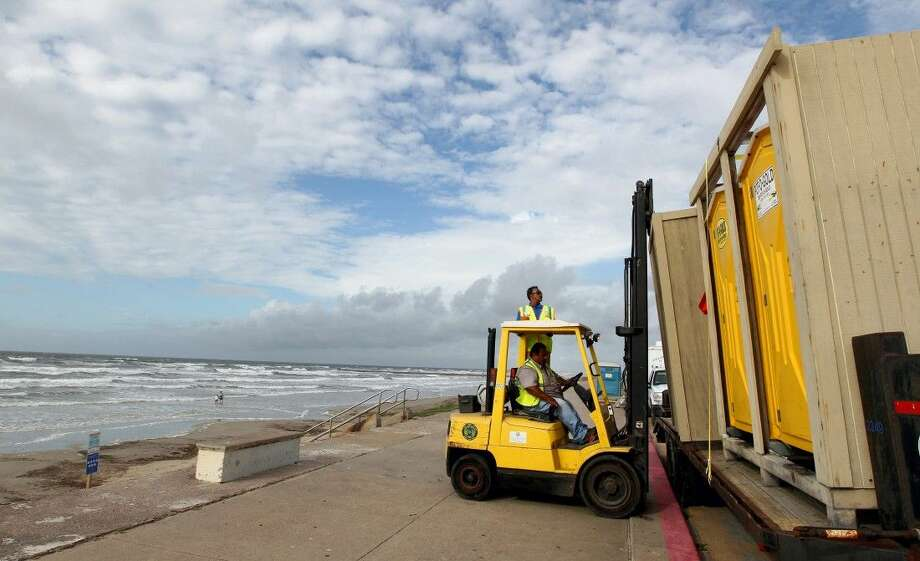 Jesse Ojeda, beach cleaning operations manager for the Galveston Island Park Board of Trustees, helps Rey Soto load portable toilets onto a trailer, Monday as they prepare the seawall for the tropical disturbance headed toward the Gulf coast.