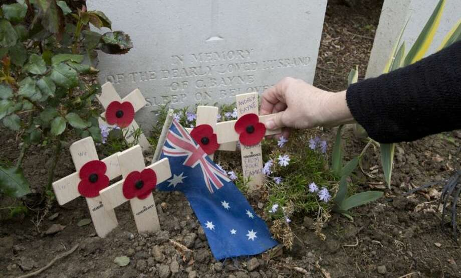 In this April 24 photo, Kaylene Biggs, great-granddaughter of World War I Australian soldier Andrew Bayne, places a wooden cross with a poppy and a message on the grave at Westhof Farm Commonwealth Cemetery in Nieuwkerke, Belgium.