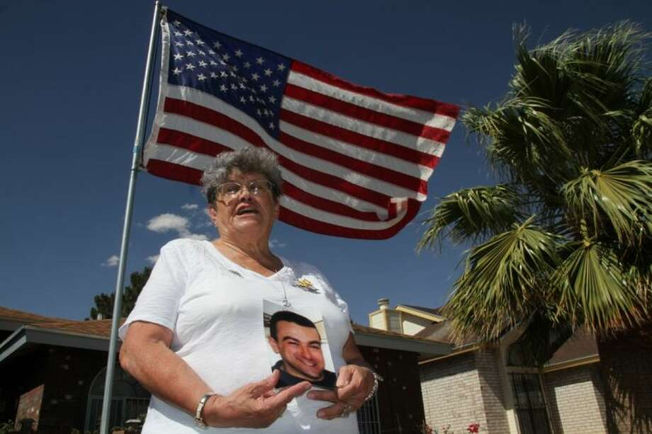 "Lillian ""Bonnie"" D'Amico, poses for a photograph while holding a photo of her son Nicholas D'Amico in El Paso Wednesday. Her son killed himself while waiting for a an appointment with a psychiatrist. Some Veterans Affairs facilities in Texas have among the longest wait-times in the nation for those trying to see a doctor for the first time, according to federal data released Monday."