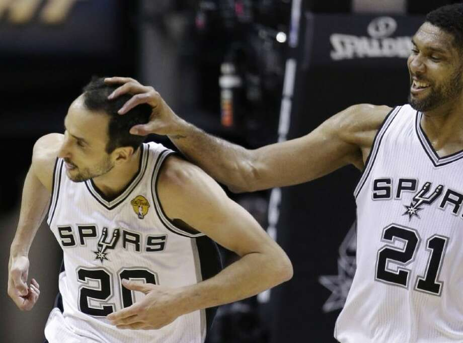 San Antonio Spurs guard Manu Ginobili, left, is congratulated by forward Tim Duncan after Ginobili dunked in the first half. The Spurs won 104-87 to take the NBA Finals. Photo: David J. Phillip