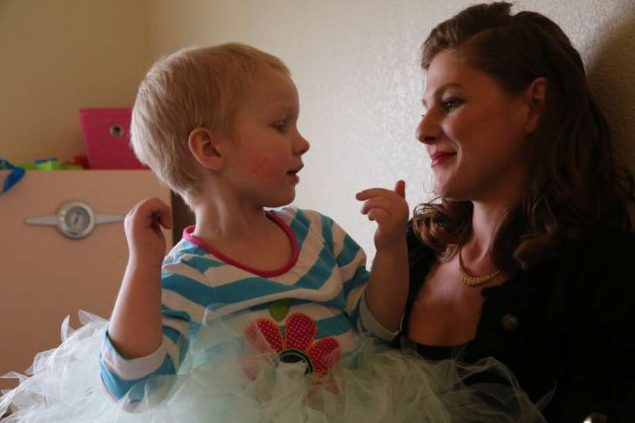 In this April 29, 2014 photo, mother of child with cancer Moriah Barnhart plays with her three year old daughter Dahlia at their home in Colorado Springs. Barnhart, frustrated with mainstream medical treatments and facing the possibility of intervention by child protective authorities, moved to Colorado to treat Dahlia using what some describe as cutting edge cannabis medication. Hundreds of parents in similar situations find themselves at the center of a debate about how far government can and should reach when parents push against legal boundaries to save their childrens' lives. (AP Photo/Brennan Linsley) Photo: Brennan Linsley