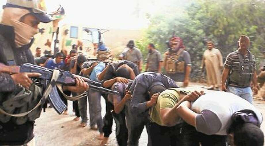 This image posted on a militant website on Saturday, June 14, 2014, which has been verified and is consistent with other AP reporting, appears to show militants from the al-Qaida-inspired Islamic State of Iraq and the Levant (ISIL) leading away captured Iraqi soldiers dressed in plain clothes after taking over a base in Tikrit, Iraq. / AP2014