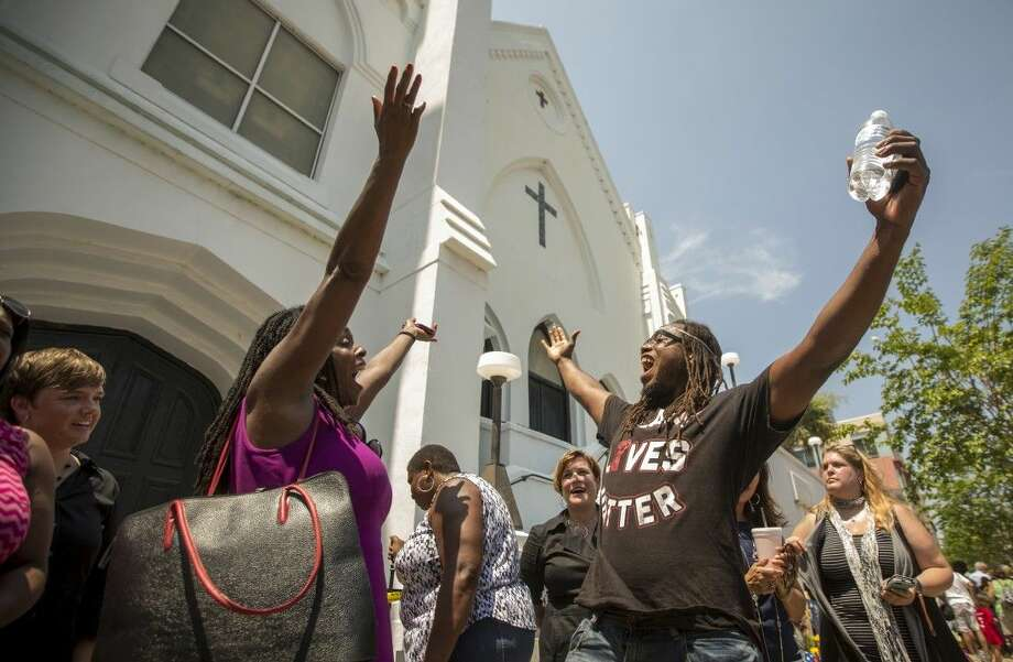 Rev. Jacqueline J. Lewis, left, and Muhiyidin D'Baha, right, leads those in attendance in a song at the memorial in front of the Emanuel AME Church, Friday in Charleston, S.C. Photo: Stephen B. Morton