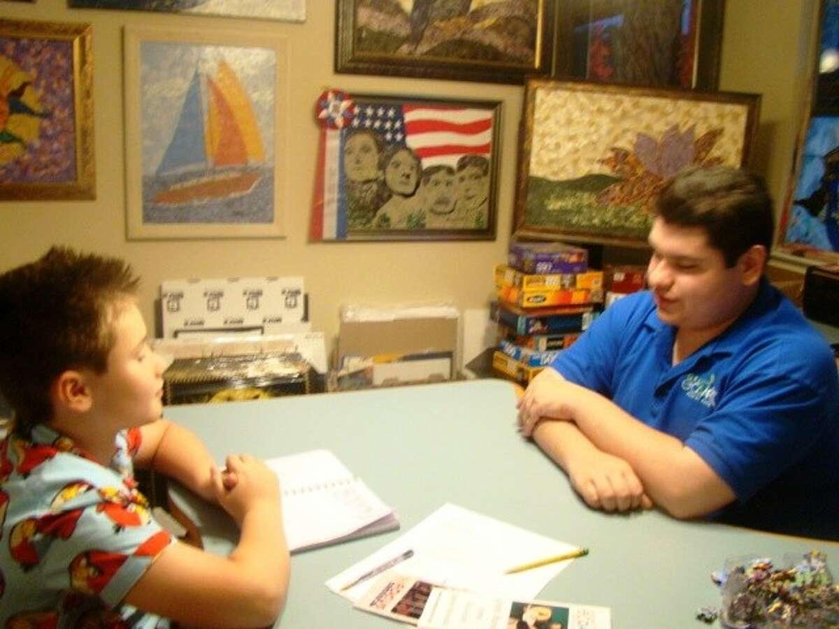 Bush Elementary student Ashton Godfrin, left, interviews Eco-Artist Grant Manier for a magazine competition.