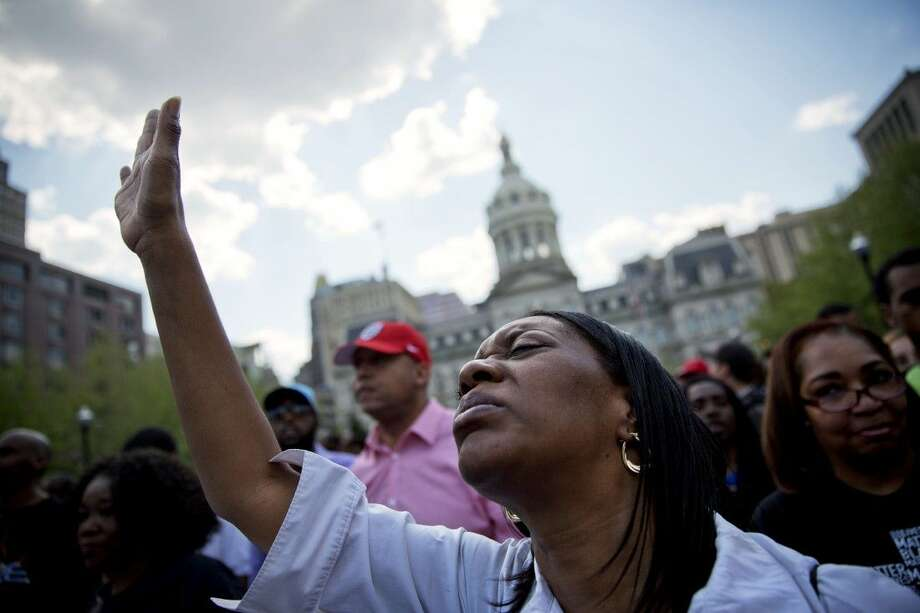 Patricia Freeman prays during a rally in front of City Hall Sunday in Baltimore. Photo: David Goldman