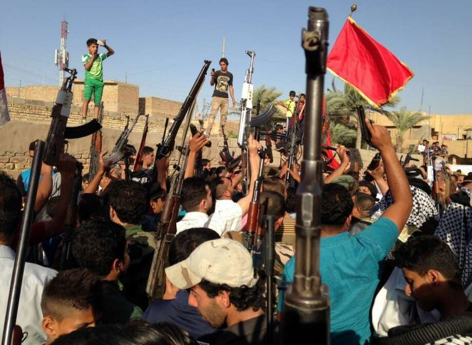 Shiite tribal fighters raise their weapons and chant slogans against the al-Qaida-inspired Islamic State of Iraq and the Levant (ISIL) in the east Baghdad neighborhood of Kamaliya, Iraq, Sunday, June 15, 2014. Emboldened by a call to arms by the top Shiite cleric, Iranian-backed militias have moved quickly to the center of Iraq's political landscape, spearheading what its Shiite majority sees as a fight for survival against Sunni militants who control of large swaths of territory north of Baghdad. Photo: Uncredited