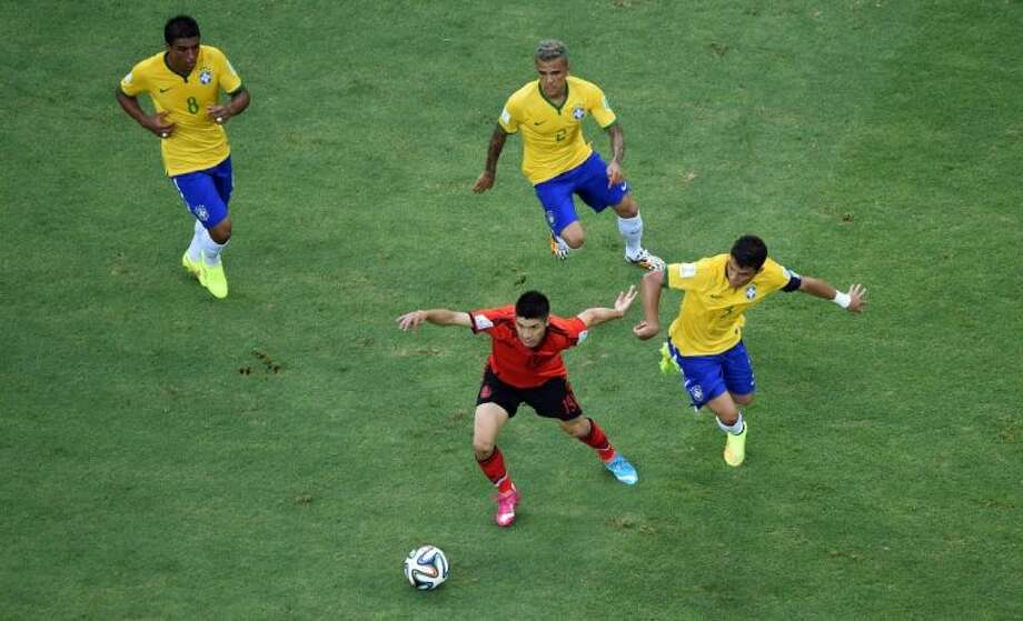 From left, Brazil's Paulinho, Dani Alves and Thiago Silva chase Mexico's Oribe Peralta during a Group A World Cup match on Tuesday at Arena Castelao in Fortaleza, Brazil. Photo: Francois Xavier Marit
