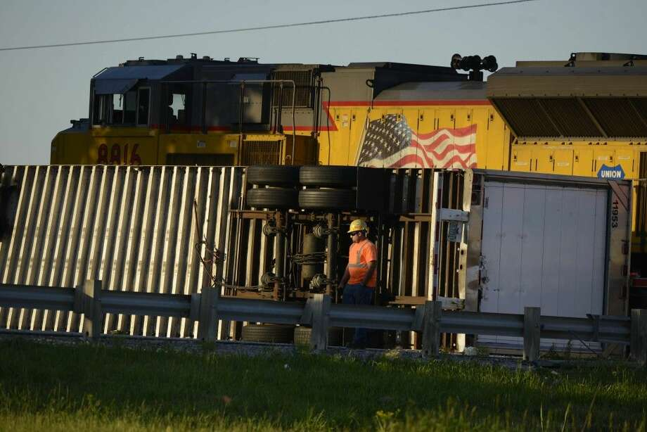 A worker stands near a semitrailer after an Amtrak train slammed into it Friday at a crossing near Wilmington, Ill. Photo: Paul Beaty