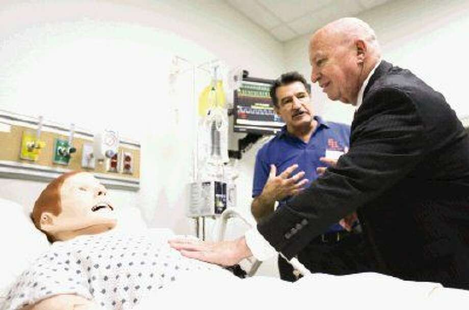 Congressman Kevin Brady feels the simulated breathing in a training mannequin for nursing students as nursing lab coordinator Ivan Najera explains how it works on Monday during a tour of the new nursing facilities at the Sam Houston State University Woodlands Center. Photo: Michael Minasi