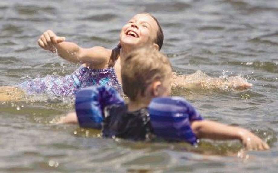 Rachel Kersten laughs as she plays in the water during a trip to Lake Conroe Park Tuesday. Lake Conroe and many places in Montgomery County are becoming a top vacation destination for families. Photo: Jason Fochtman / Conroe Courier / HCN