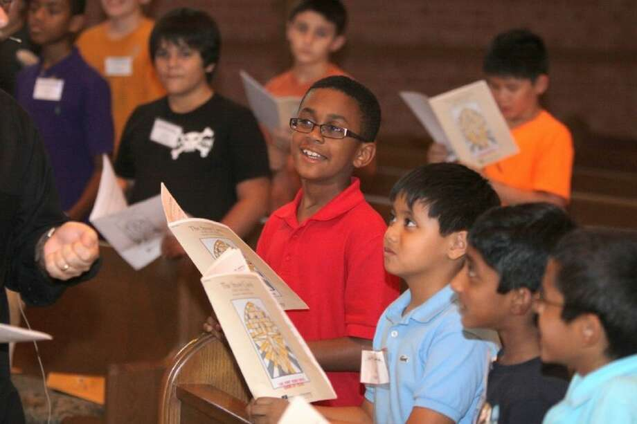 Members of the Fort Bend Boy's Choir listen to instruction by Matt Robinson at singing practice.