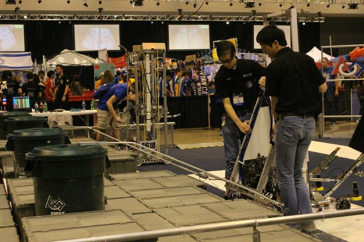 Two Texas Torque teammates begin assembling the robot at the competition stage. The task was to assemble a tower of storage boxes and set a plastic trash can on top.