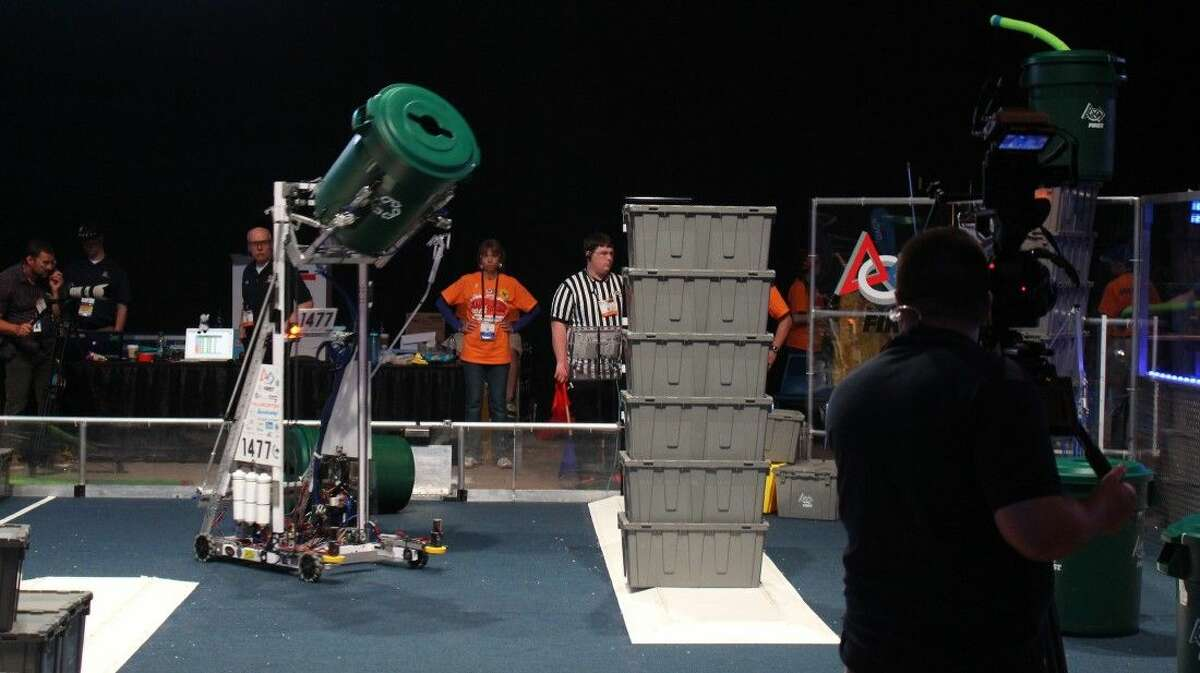 Texas Torque's robot attempts to set a plastic trash can on top of the already-completed box tower - one of the ways the teams can earn points toward advancing.