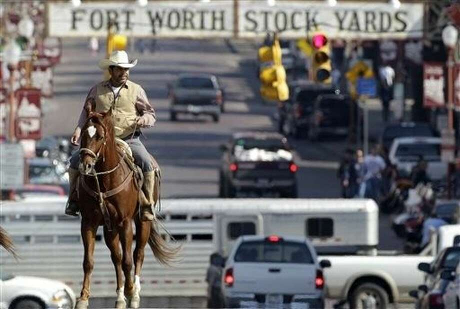 FILE - In this Jan. 30, 2011, file photo, Antonio Hinojosa, natively of Zacatecas, Mexico, currently living in Fort Worth, rides his horse up Exchange Ave. , in the historic Fort Worth Stockyards, which was identified by the National Trust for Historic Preservation as one of America's 11 most endangered historic places. Photo: Tony Gutierrez