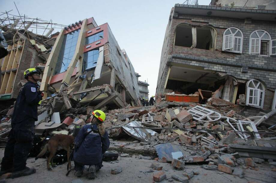 USAID rescue workers inspect the site of collapsed buildings after an earthquake in Kathmandu, Nepal, Tuesday. Photo: Bikram Rai