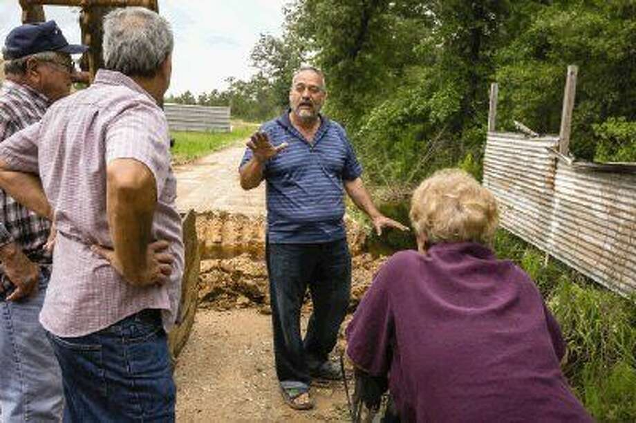 Residents of Greenbough Road met with Jesse Gonzalez, owner of Thunder Gun Range, center, to look around the range and discuss their grievances on Tuesday about flooding on their properties that they allege is due to developments on the gun range.