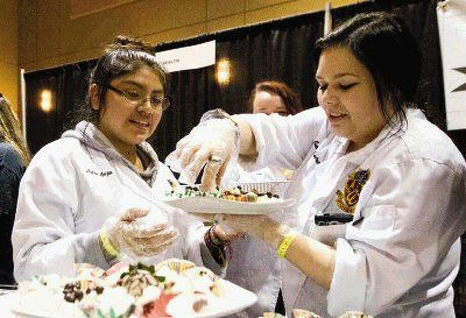 Julia McGuire and Aylin Leija, Caney Creek students with Conroe ISD's Culinary Arts Academy, plate food during Tastefest at the Lone Star Convention & Expo Center on Thursday. Go to HCNpics.com view more photos from the event. Photo: Jason Fochtman