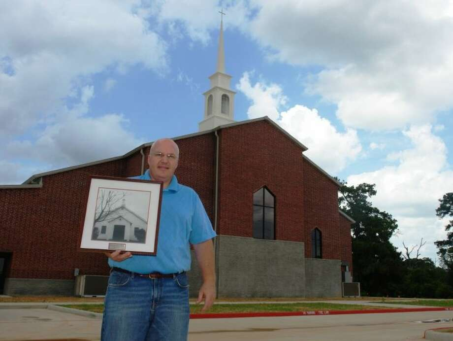 Pastor Wes Pratt holds a photo of the original Northside Baptist Church building in 1944 as he stands in front of the new church sanctuary at 701 N. FM 3083 West in Conroe.